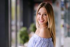 Schönes blondes Mädchen, das zuhause Porträt aufwirft stockfoto