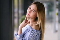Schönes blondes Mädchen, das zuhause Porträt aufwirft stockfotografie