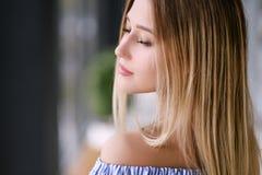 Schönes blondes Mädchen, das zuhause Porträt aufwirft lizenzfreie stockfotos