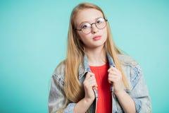 Schönes blondes Mädchen in den Gläsern, die Kamera betrachten Lizenzfreie Stockfotos