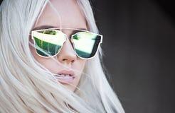 Schönes blondes Mädchen in den grünen sunglassses im Freien Stockfoto