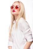 Schönes blondes Mädchen in den rosa Gläsern und im Hemd Schönes lächelndes Mädchen Getrennt auf weißem Hintergrund Stockfotos