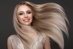 Schönes blondes Mädchen in der Bewegung mit einem tadellos glatten Haar und klassisches Make-up Schönes lächelndes Mädchen lizenzfreies stockfoto