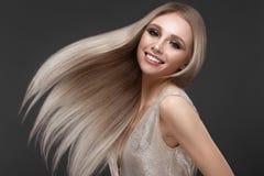 Schönes blondes Mädchen in der Bewegung mit einem tadellos glatten Haar und klassisches Make-up Schönes lächelndes Mädchen lizenzfreies stockbild