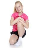 Schönes blondes Mädchen in der roten Strickjacke und Lizenzfreies Stockfoto