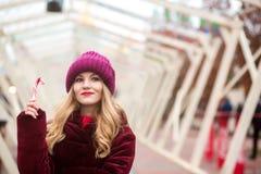 Schönes blondes Mädchen in der roten Strickmütze, die mit Zuckerstange aufwirft Stockbild