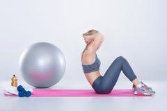 Schönes blondes Mädchen in der Sportkleidung tut Übungen auf Eignung Matte auf grauem Hintergrund Stockbilder