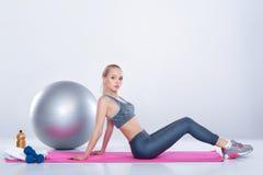 Schönes blondes Mädchen in der Sportkleidung tut Übungen auf Eignung Matte auf grauem Hintergrund Lizenzfreies Stockfoto