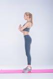 Schönes blondes Mädchen in der Sportkleidung tut Übungen auf Eignung Matte auf grauem Hintergrund Stockfotos