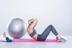 Schönes blondes Mädchen in der Sportkleidung tut Übungen auf Eignung Matte auf grauem Hintergrund Stockfotografie