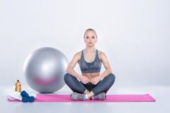 Schönes blondes Mädchen in der Sportkleidung tut Übungen auf Eignung Matte auf grauem Hintergrund Stockbild