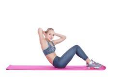 Schönes blondes Mädchen in der Sportkleidung tut Übungen auf Eignung Matte auf weißem Hintergrund Stockbilder