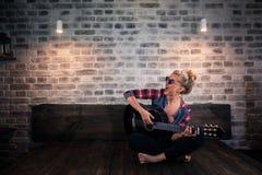 Schönes blondes Mädchen in der verursachenden Musik auf Gitarre spielenden und singenden Kleidung Lizenzfreie Stockfotos