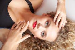 Schönes blondes Mädchen des Porträts bilden das Lügen auf Bodenatelieraufnahme Stockbilder