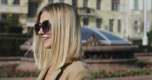 Schönes blondes Mädchen des Porträts in der Sonnenbrille in einer Stadt stock video footage