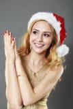 Schönes blondes Mädchen in einem Goldkleid und -hut bereit zu Christma Stockbild