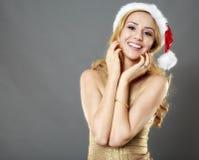 Schönes blondes Mädchen in einem Goldkleid und -hut bereit zu Christma Lizenzfreies Stockfoto