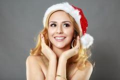 Schönes blondes Mädchen in einem Goldkleid und -hut bereit zu Christma Stockfotografie