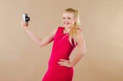 Schönes blondes Mädchen in einem hellen Kleid fotografierte sich Stockfotografie