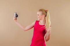 Schönes blondes Mädchen in einem hellen Kleid fotografierte sich Stockfoto