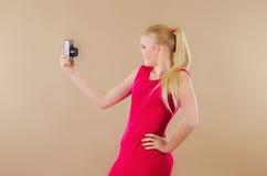 Schönes blondes Mädchen in einem hellen Kleid fotografierte sich Stockbilder