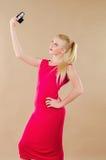 Schönes blondes Mädchen in einem hellen Kleid fotografierte sich Lizenzfreies Stockfoto