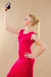 Schönes blondes Mädchen in einem hellen Kleid fotografierte sich Lizenzfreie Stockfotografie