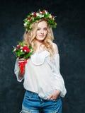 Schönes blondes Mädchen in einem Kranz von Blumen Stockbild