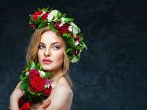 Schönes blondes Mädchen in einem Kranz von Blumen Lizenzfreies Stockfoto