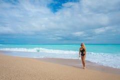 Schönes blondes Mädchen in einem schwarzen Badeanzug auf einem leeren karibischen Strand Stockbild