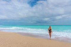 Schönes blondes Mädchen in einem schwarzen Badeanzug gehend auf einen leeren karibischen Strand Stockfotografie