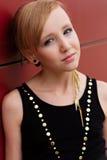 Schönes blondes Mädchen in einem schwarzen Kleid, das gegen eine rote Wand aufwirft Lizenzfreie Stockfotos