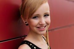 Schönes blondes Mädchen in einem schwarzen Kleid, das gegen eine rote Wand aufwirft Stockbild