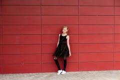 Schönes blondes Mädchen in einem schwarzen Kleid, das gegen eine rote Wand aufwirft Stockfoto