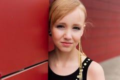 Schönes blondes Mädchen in einem schwarzen Kleid, das gegen eine rote Wand aufwirft Stockbilder