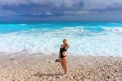 Schönes blondes Mädchen in einer schwarzen Badebekleidung, die auf einem leeren karibischen Strand aufwirft Stockbilder
