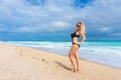 Schönes blondes Mädchen in einer schwarzen Badebekleidung, die auf einem leeren karibischen Strand aufwirft Lizenzfreies Stockbild
