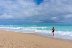 Schönes blondes Mädchen in einer schwarzen Badebekleidung gehend auf einen leeren karibischen Strand Stockbild