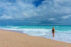 Schönes blondes Mädchen in einer schwarzen Badebekleidung gehend auf einen leeren karibischen Strand Stockbilder