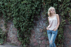 Schönes blondes Mädchen in einer Weste und in den Jeans steht nahe Wand mit Rebe auf Stadtstraßen Stockfoto