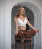Schönes blondes Mädchen fliegt in den Lotussitz im weißen Innenraum mit Bogen Lizenzfreie Stockfotos