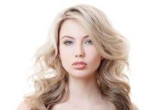 Schönes blondes Mädchen. Gesundes langes gelocktes Haar. Lizenzfreies Stockfoto
