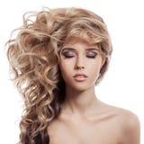 Schönes blondes Mädchen. Gesundes langes gelocktes Haar. Stockbild