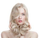 Schönes blondes Mädchen. Gesundes langes gelocktes Haar. Lizenzfreie Stockfotos