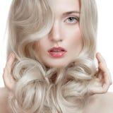 Schönes blondes Mädchen. Gesundes langes gelocktes Haar. Stockfotografie