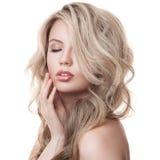 Schönes blondes Mädchen. Gesundes langes gelocktes Haar. Stockbilder