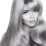 Schönes blondes Mädchen. Gesundes langes gelocktes Haar.  Modeschwarzes a Lizenzfreie Stockbilder