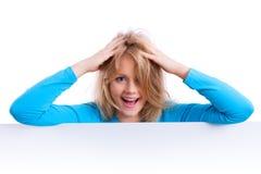 Schönes blondes Mädchen hinter einem leeren weißen Brett, lokalisiert Lizenzfreies Stockfoto