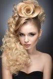 Schönes blondes Mädchen im Abendkleid mit einer ungewöhnlichen Frisur in Form von Rosen und hellem Make-up Schönes lächelndes Mäd Lizenzfreie Stockfotografie