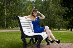 Schönes blondes Mädchen im blauen Kleid, das auf einer Bank im Sommer sitzt Stockbild